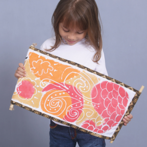 young girl holding self-made Indonesian batik art