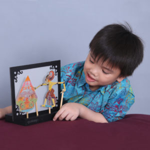 young boy admiring self-made Indonesian wayang kulit