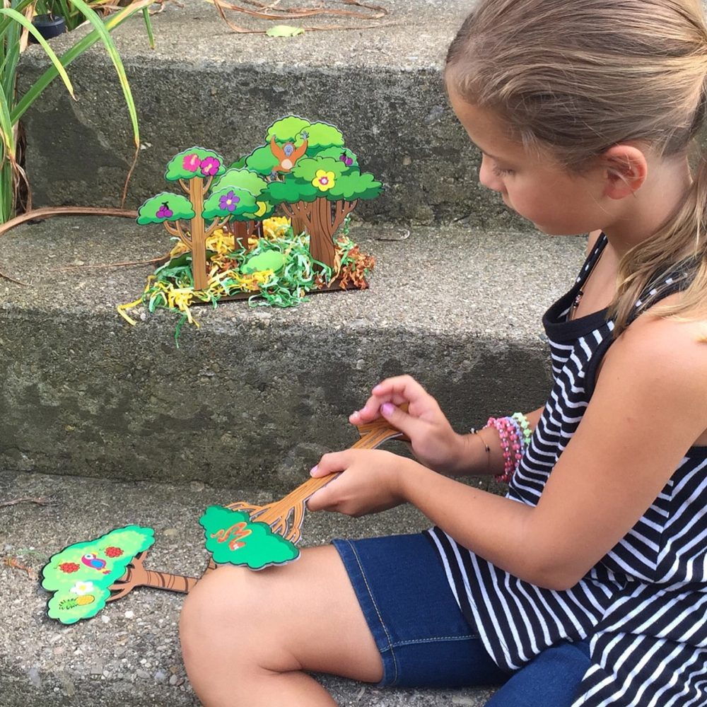 girl focused on making gummybox rainforest diorama