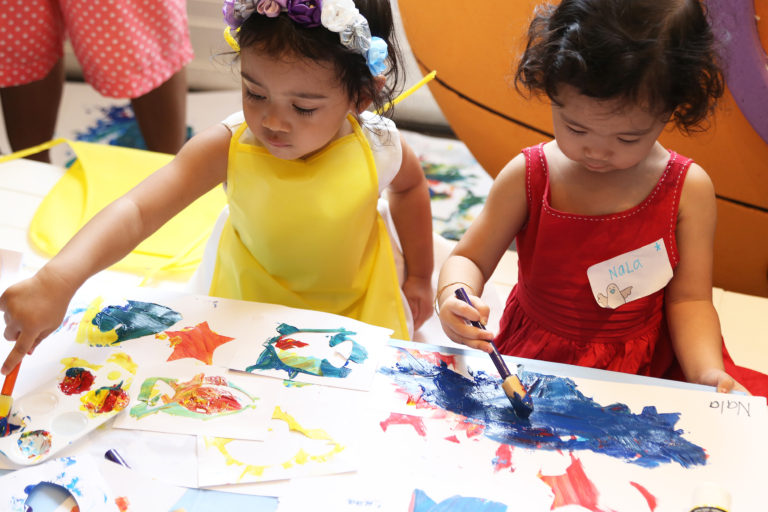 two kids sitting and painting creatively